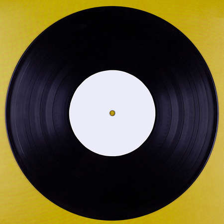 An old vinyl record with an empty label isolated against a mustard-colored background