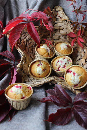 Fresh cupcakes with cherry filling are placed in a wicker basket and decorated with autumn leaves