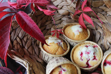 Fresh cherry filled cupcakes in a wicker basket.Texture or background