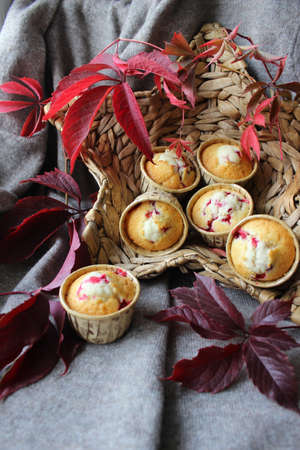 Fresh cupcakes in the basket are decorated with autumn leaves Banco de Imagens