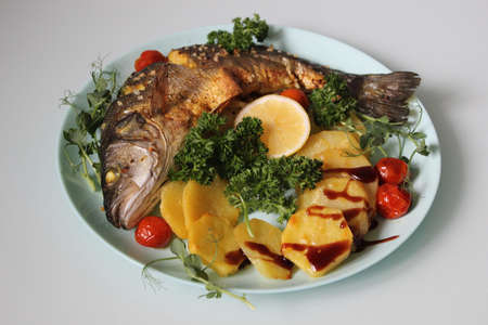Fried fish with potatoes on a plate close-up.Texture or background Banco de Imagens