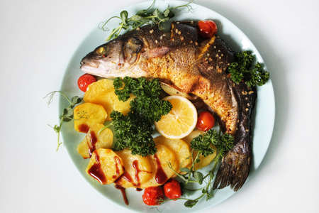 Close-up of fried fish and potatoes decorated with a slice of lemon
