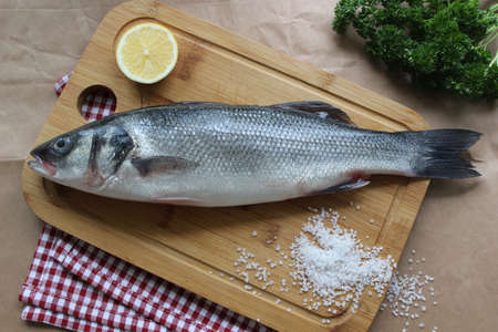One raw fish on a wooden chopping Board is decorated with a lemon slice in close-up Banco de Imagens
