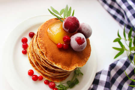 Pancakes are decorated with frozen cherries on a white plate