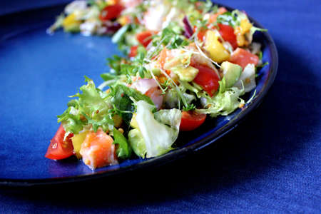 Fresh salad with tomatoes and herbs on a blue plate.Health food. Banco de Imagens