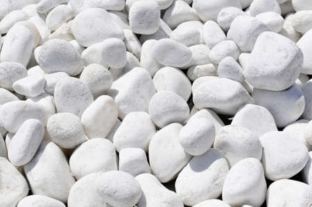 Beach large white stones of different sizes illuminated by the sun.
