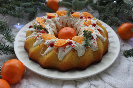 Round Christmas dessert is decorated with tangerine slices on a white plate