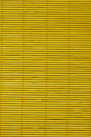 Wooden blinds on the mustard-colored windows.Texture or background