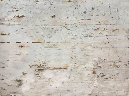 Outdoors, beige paint flakes off the surface of the wall in close-up