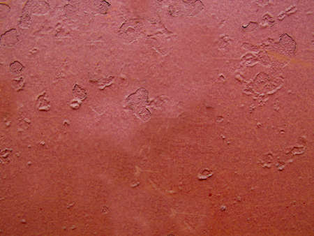 Damaged old maroon wall close-up with detailed texture Archivio Fotografico