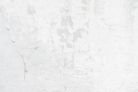 A concrete white wall with a cracked and peeling surface Archivio Fotografico
