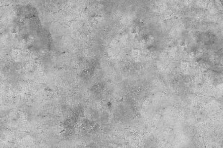Textured grey concrete wall with cracks on the surface