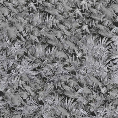 Black and white ice frost crystals on the glass