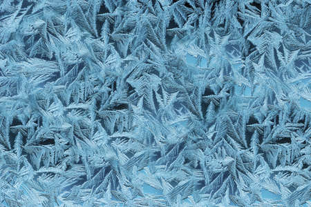 Textured patterns are drawn by frost on the windows of houses