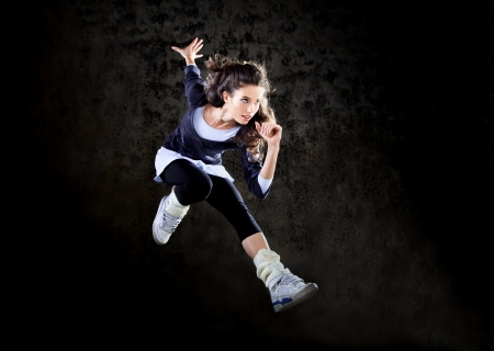 Dancing woman with brown long hair and happy facial expression jumping up
