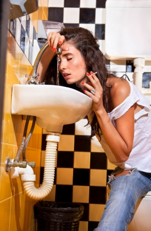 Young upset woman with sickness holding cigarette into toilet