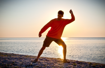 chi kung: Young attractive man making Thai-chi movements on the beach of Black sea Stock Photo