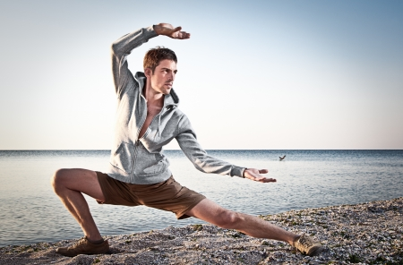 Young attractive man making Thai-chi movements on the beach of Black sea Stock Photo