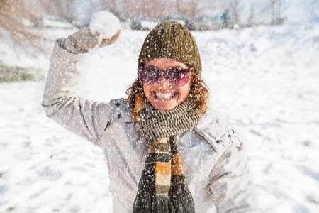 Happy young woman playing snowball fight on the snow  day   Winter concept  photo