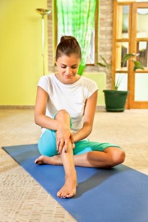 masaje deportivo: Mujer joven feliz haciendo masaje de la pierna libre en la vida familiar sana