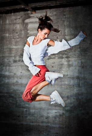 dancing pose: Dancing woman with brown long hair and happy facial expression jumping up