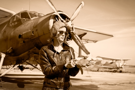 aviators: Portrait of beautiful female pilot with plane behind  Sepia