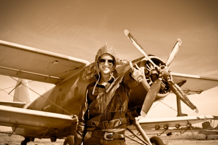 aviators: Portrait of beautiful female pilot with plane behind  Sepia photo