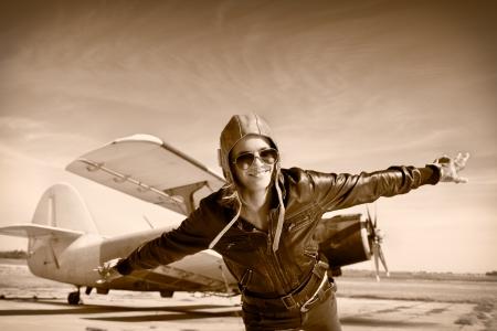 pilotos aviadores: Mujer joven feliz con las manos en alto vuelo en el aeropuerto Foto de archivo