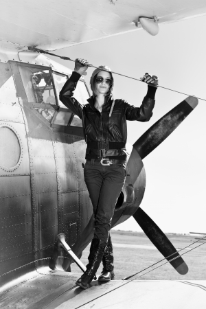 Beautiful girl in black jacket standing on a war aircraft  Retro black and white photo