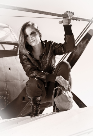 Beautiful girl in black jacket standing on a war aircraft