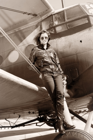 Beautiful girl in black jacket standing on a war aircraft    Stock Photo