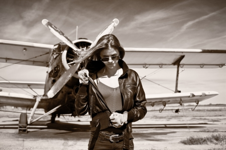 depart: Beautiful girl in black jacket standing with aircraft behind
