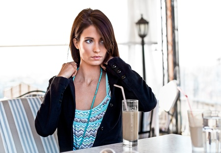 Portrait of cute young business woman while drinking her ice coffee at outdoor cafe photo