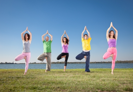 People in group  practice Yoga asana on lakeside  Yoga concept  photo