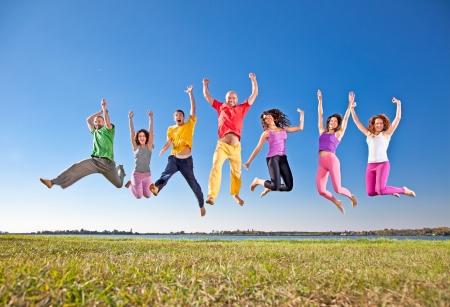 springende mensen: Happy lachende groep springen mensen op banch van het meer Stockfoto