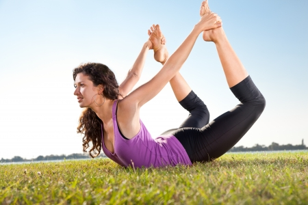 Beautiful young woman doing stretching exercise on green grass next to the  lake  Yoga concept  Stock Photo