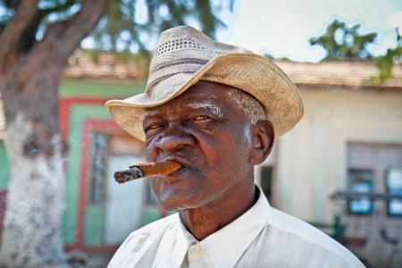 cigarro: TRINIDAD, CUBA -13 de enero: El hombre fuma un cigarro cubano el 13 de enero. 2010.Trinidad, Cuba. Los cubanos de todas las edades est�n fumando cigarros activamente. Toda la producci�n en Cuba est� controlado por el gobierno cubano