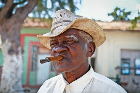 actively: TRINIDAD,CUBA -13 JANUARY:Cuban man smoking a cigar on January 13. 2010.Trinidad,Cuba. Cubans of all ages are actively smoking cigars. All the production in Cuba is controlled by the Cuban government