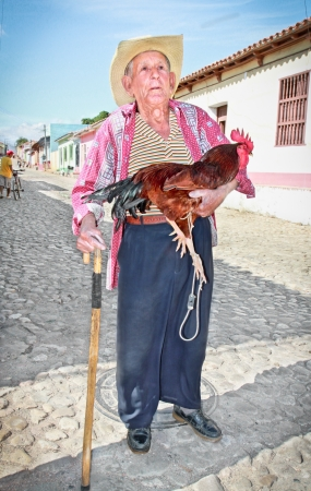 TRINIDAD,CUBA-13 JANUARY: Unidentified farmer holding a rooster on the street of Trinidad on January 13. 2010. Trinidad, Cuba. Working in tourism is the only way Cuban people can earn a decent income.