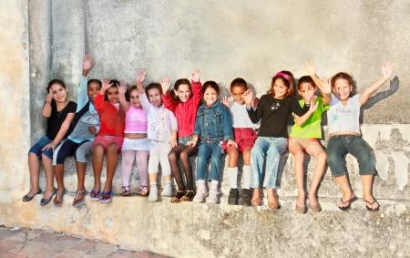 niños jugando en el parque: TRINIDAD, CUBA -13 de enero: no identificados grupo multiétnico cubana de las niñas están sentados y los brazos levantados en la calle principal de Trinidad, el 13 de enero. 2010. Trinidad, Cuba.