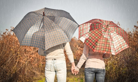 couple in rain: Young couple under an umbrella in the autumn forest