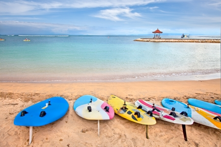 Surf boards on idyllic tropical sand Nusa Dua beach, Bali, Indonesia. Stock Photo