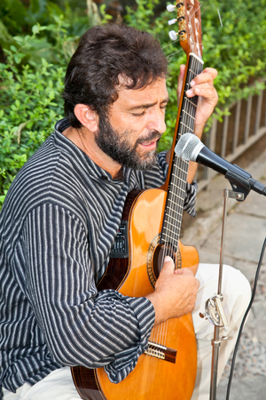 SEVILLE, SPAIN - SEP 11: Male musician playing in the street for money on Sep 11, 2011, in Seville, Spain. Spain is going through economic hardship these days.