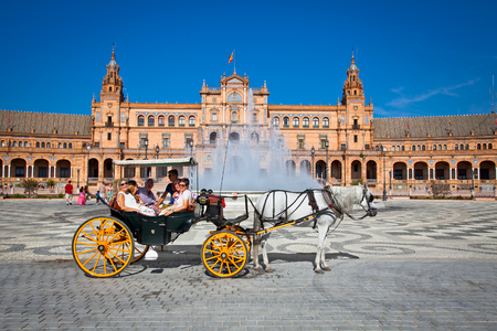 SEVILLE, SPAIN-SEP 10:Tourists enjoy a trip on horsedrawn cart on Plaza de Espana, Seville on Sep 10. 2011.Plaza de Espana was built in 1929 is a huge half-circle with total area of 50,000 square m.  報道画像