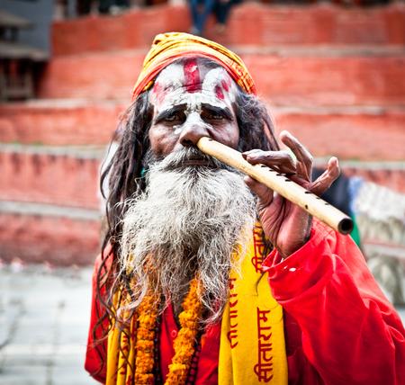 KATHMANDU,NEPAL-MAY 18: Sadhu play flute at Pashupatinath Temple in Kathmandu, Nepal on May 18, 2013. The two primary sectarian divisions in sadhu community are Shaiva sadhus and Vaishnava sadhus. Editorial