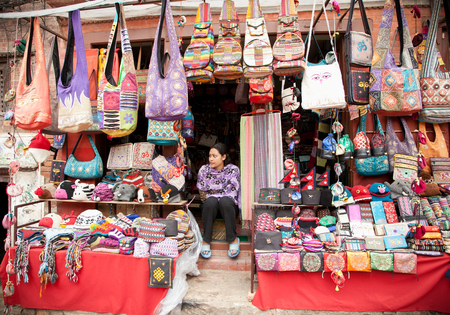 PATAN - MAY 20 : Unidentified woman sitting on the stairs in front of his shop in Patan, Nepal on May 20, 2013. Patan is best known for its rich cultural heritage, expecially its arts and crafts.