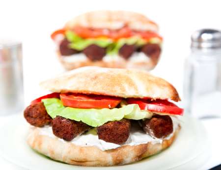 Oval vegan sandwich made from integral bred with soya barbecue cevapcici, soya cheese, onion, tomato and  lettuce serve on plate Reklamní fotografie
