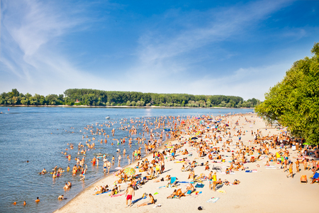 NOVI SAD, SERBIA -AUGUST 4, 2013: Group of unidentified people having daytime chill out on the public beach on Danube river after the hard hot summer night at on August 4, 2013.