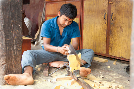 BHAKTAPUR, NEPAL-MAY 20: Unidentified carpenter sawing a board  in Bhaktapur, Nepal, on May 20. 2013. Much of Nepals economy still relies on hand tools and skilled tradesmen.