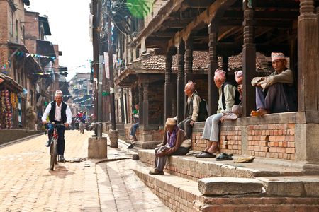 BHAKTAPUR - MAY 20 : Unidentified Tharu old men besides the street of Bhaktapur, Nepal on May 20, 2013. Tharu are an ethnic group from west part of Nepal. Editorial